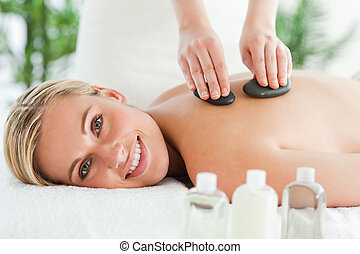 Blonde smiling woman experiencing a stone therapy in a...