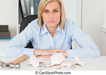 Sad woman sitting in her office in front of an shattered...