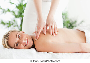 Blonde smiling woman relaxing on a lounger during massage in...