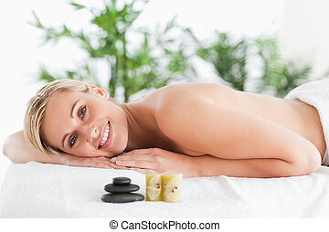 Smiling blonde woman lying on a lounger with stones and...