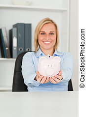 Gorgeous businesswoman holding a piggy bank