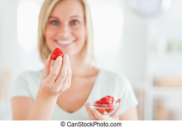 Close up of a woman enjoying eating strawberries looking into the camera in the kitchen