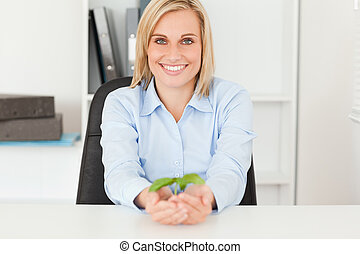 Woman holding a little plant smiies into camera in her...