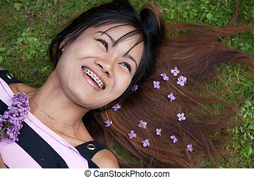 Thai womanwith a big smile laying on the grass