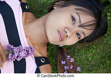 Young Thai woman laying on the grass