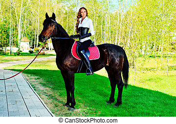 equitation - Beautiful young woman with a horse outdoor
