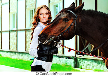 dressage - Beautiful young woman with a horse outdoor