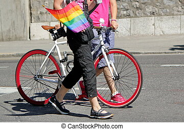Gaypride and bicycle - Two persons walking next to a red...