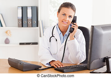 Serious female doctor on the phone in her office