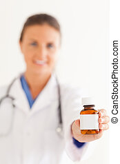 Close up of a cute doctor handing over some pills in the...