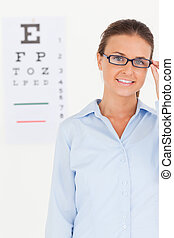 Good looking brunette eye specialist wearing glasses looking into the camera in her surgery