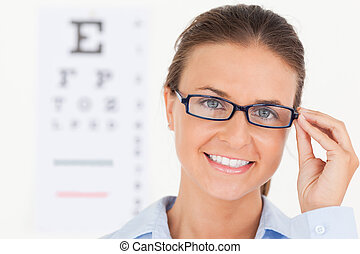 Close up of a good looking brunette eye specialist wearing glasses looking into the camera in her surgery