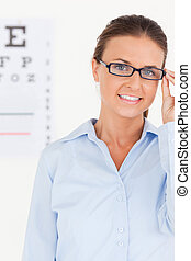 Portrait of a brunette eye specialist wearing glasses looking into the camera in her surgery