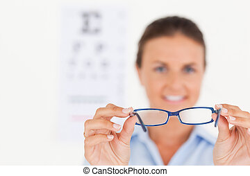 Portrait of a brunette eye specialist handing out glasses smiling into the camera in her surgery