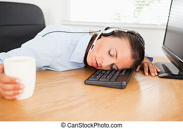 Businesswoman with headset sleeping in office - A...