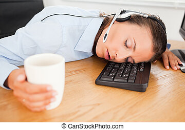 Businesswoman with headset sleeping in office with coffee
