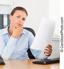 Close up of a thinking businesswoman holding a paper