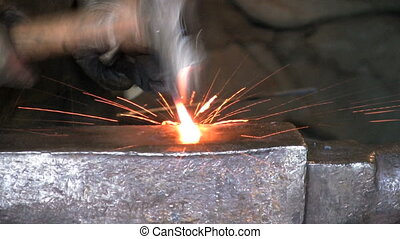 Blacksmith Flattening Metal - A blacksmith flattening a hot...