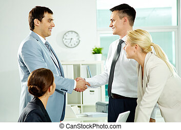 Congrats - Portrait of successful associates handshaking...