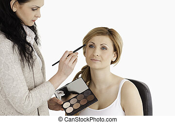 Cute blond-haired woman having her make up done by a make up artist in a studio