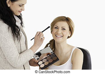 Attractive blond-haired woman having her make up done by a make up artist in a studio