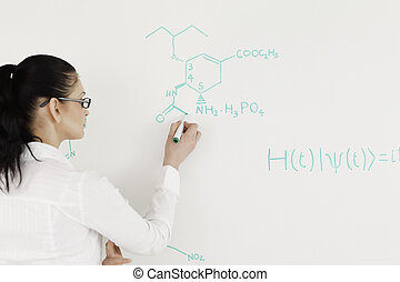 Scientist writing a formula on a white board