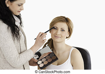Attractive woman having her make up done by a make up artist