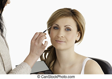 Make-up artist applying make up to a blond-haired woman