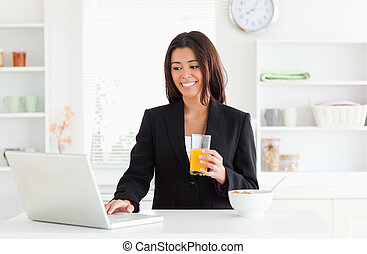 Charming woman in suit relaxing with her laptop while holding a glass of orange juice in the kitchen