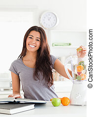 Good looking woman consulting a notebook while filling a blender with fruits in the kitchen