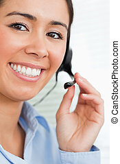 Portrait of a beautiful female with a headset helping customers while sitting at the office