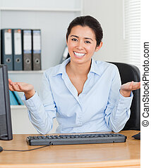 Proud attractive woman posing while sitting at the office