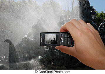 Taking Pictures With Mobile Phone - Cell phone with hand...