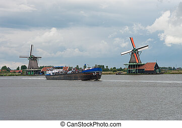 windmills at the zaanse schans in Holland - barge passing by...