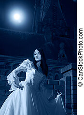 Woman in white dress stay near the church. Russia...