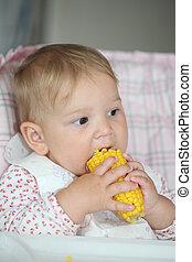 Baby girl eating cooked sweet corn