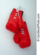 Boxing gloves - Red boxing gloves pending from a gray wall
