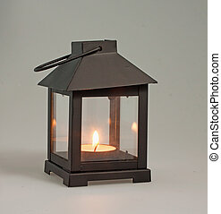 Lantern - A decorative black lantern over a black mat with...
