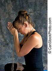 woman praying with mala beads