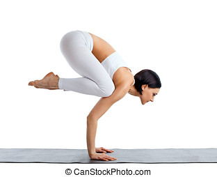 Young woman in white doing yoga pose arm balance on rubber...