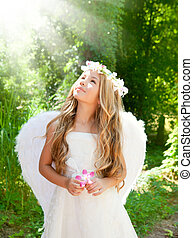 Angel children girl in forest with flower in hand looking...