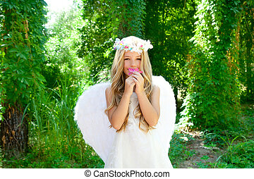 Angel children girl smelling pinks flower in forest with...