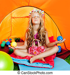 Children girl inside camping tent relaxing with yoga open...