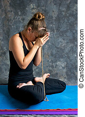 young woman praying on mat with mala beads - Studio portrait...