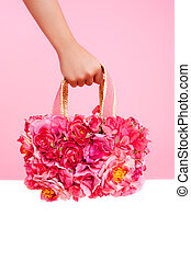 red flowers bag in woman hand on pink background