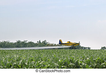 Crop Dusting - Airplane applying pesticide onto a farm field
