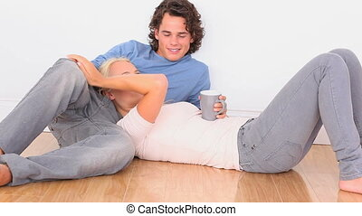 Happy couple on the floor with a cup in the livingroom
