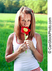 Portrait of young woman with plushy flower in hand...