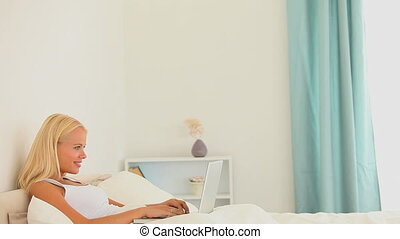 Woman with a notebook in her bed