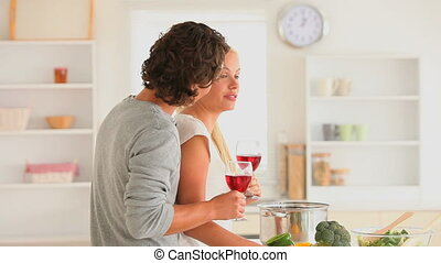 Joyful couple with wine in the kitchen